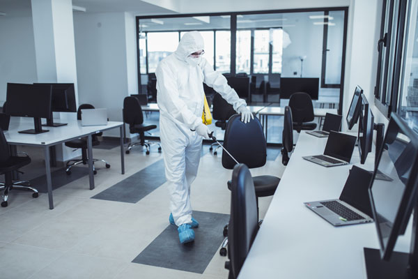 Decontamination Cleaning Services A Cleaner wearing full Personal Protective Equipment to decontaminate an office