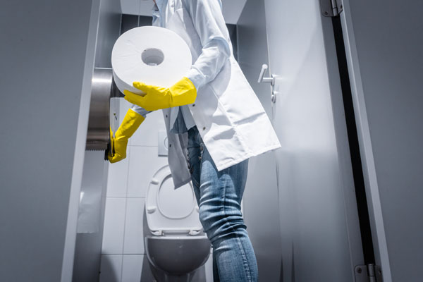 A Cleaner changing toilet roll in office toilet