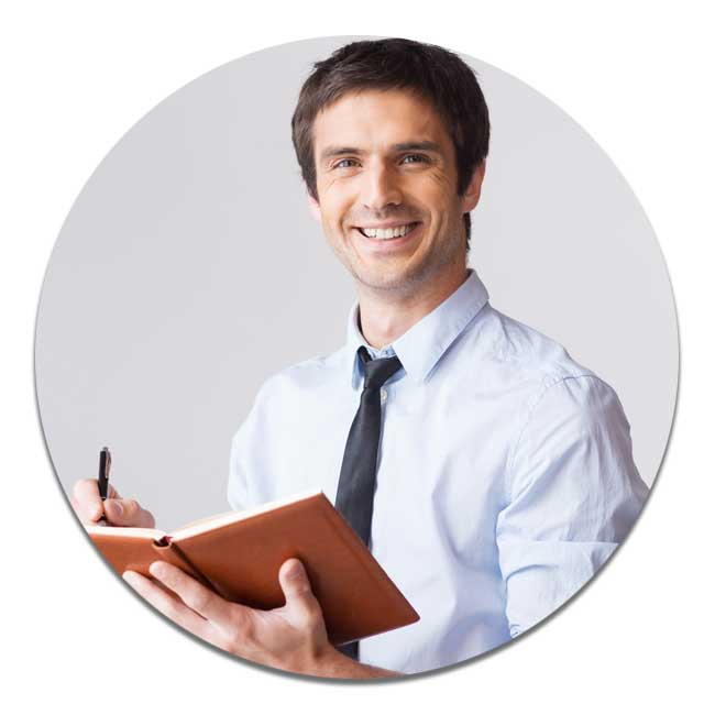 Man in a shirt and tie smiling at the camera whilst writing in a brown note book